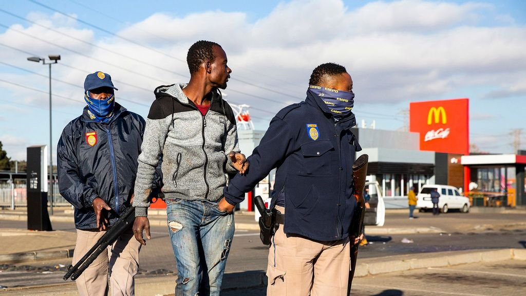 Police detain a man suspected of looting on July 13, 2021 at a shopping centre in Vosloorus, Johannesburg, South Africa. South Africa has deployed the military to quell spasms of civil unrest and looting sparked by last week's imprisonment of former president Jacob Zuma. The unrest is also fueled by high unemployment and social and economic fallout from the Covid-19 pandemic, which has hit the country hard. (James Oatway/Getty Images)